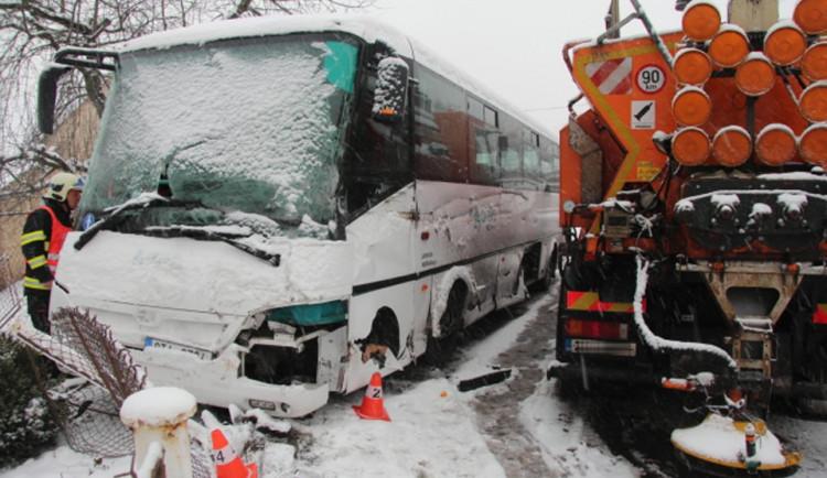 Autobus se srazil se sypačem a skončil v plotu rodinného domu, řidič byl převezen do nemocnice