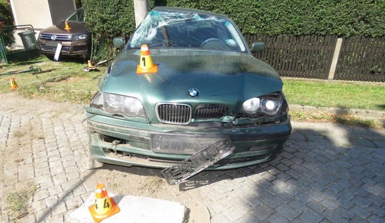 Řidič dostal smyk. Naboural zaparkované auto, plot domu a sloup vysokého napětí
