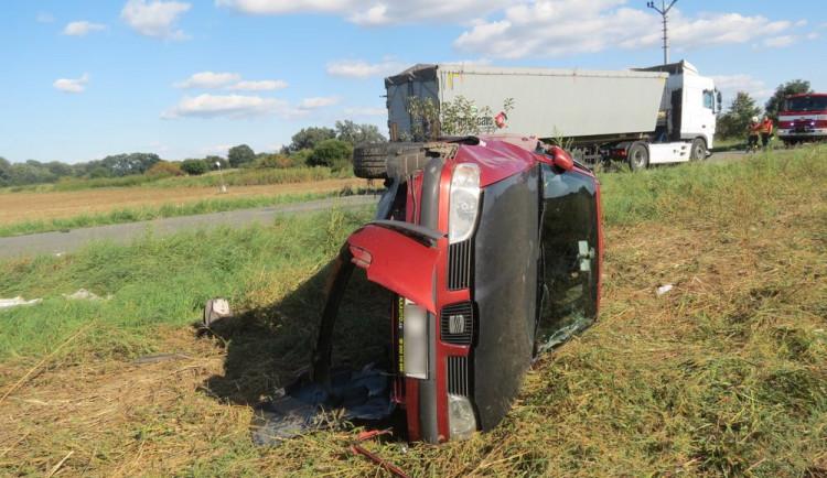 Řidič náklaďáku přehlédl pomalu jedoucí osobák a narazil do něj. Jeho řidička skončila v převráceném voze na poli
