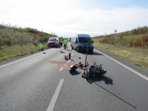Motorkář se díval do zpětného zrcátka a přehlédl auto s přívěsem před ním. Po nárazu upadl na silnici