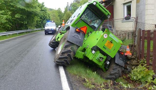 FOTO: Řidič zemědělského stroje sjel z cesty a opřel se o plot rodinného domu