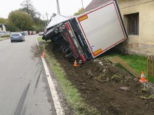 Krajnice kamion neunesla. Tahač s návěsem opřel řidič o dům
